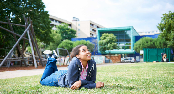 image of young person on grass outside of school